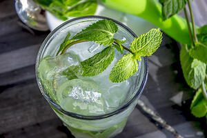 Mojito cocktail in glass with mint and lime and bar spoon