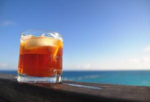 dark and stormy rum cocktail sitting on a railing on a sunny day by the ocean