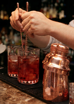 Bartender's hands mixing cocktail with two stirrers