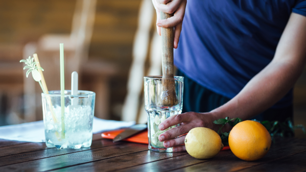 Bartender muddling fruit in glass on wood table with fruit nearby