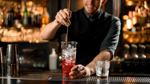 Bartender mixing red cocktail in tall glass with ice and a bar spoon