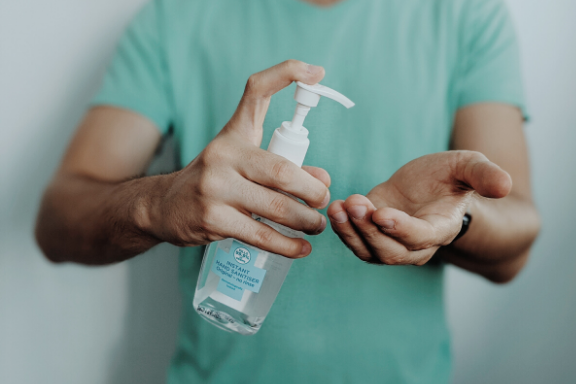 Man in green shirt on white background putting hand sanitizer on his hands