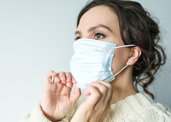Woman on blank background wearing a white sweater pulling up her face mask
