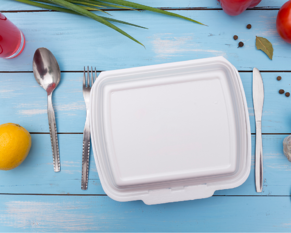 Photo of styrofoam take out container on a blue table with cutlery and fruit