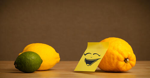 Lemon with sticky post-it note gesturing to citrus fruits