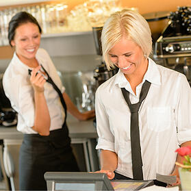 Two women behind the bar wearing work uniforms and laughing