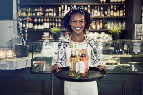 Woman holding tray of beers out and smiling in front of a bar