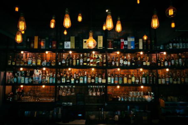 Bar shelf full of liquor bottles with soft lighting