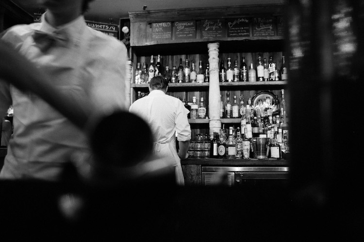 Black and white image of bar and with bar manager in background and bartender in foreground