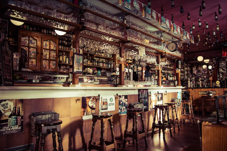 Picture of Bar with Stools and Glassware and Bartender looking at Back bar of Liquor Bottles