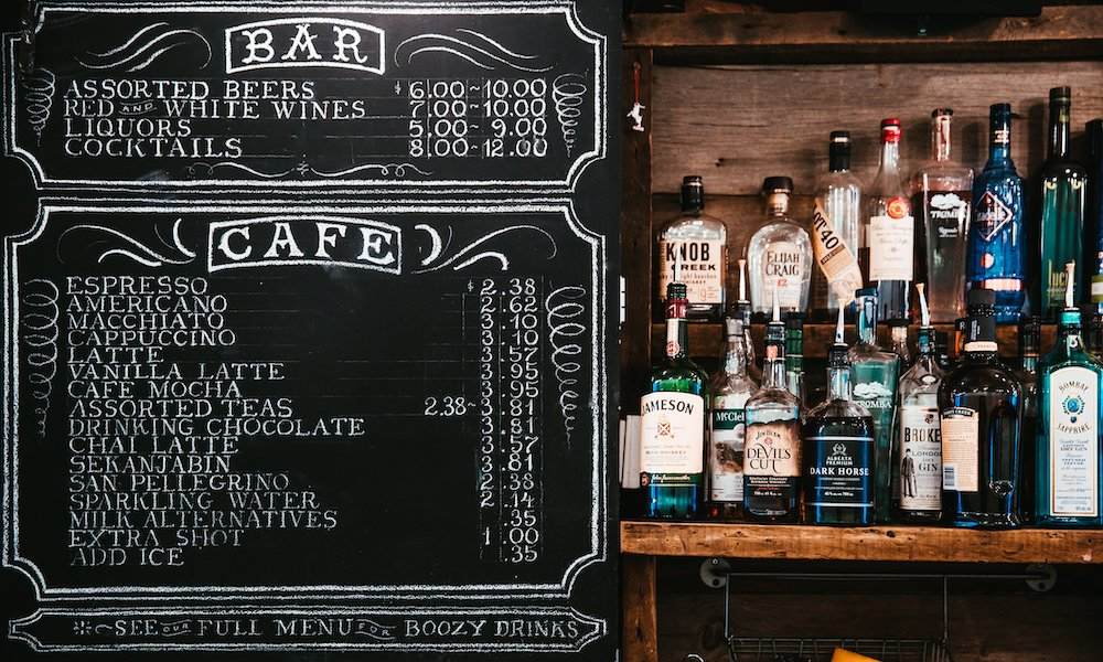 Bottles of Liquor at Bar with Costs on Chalkboard Menu