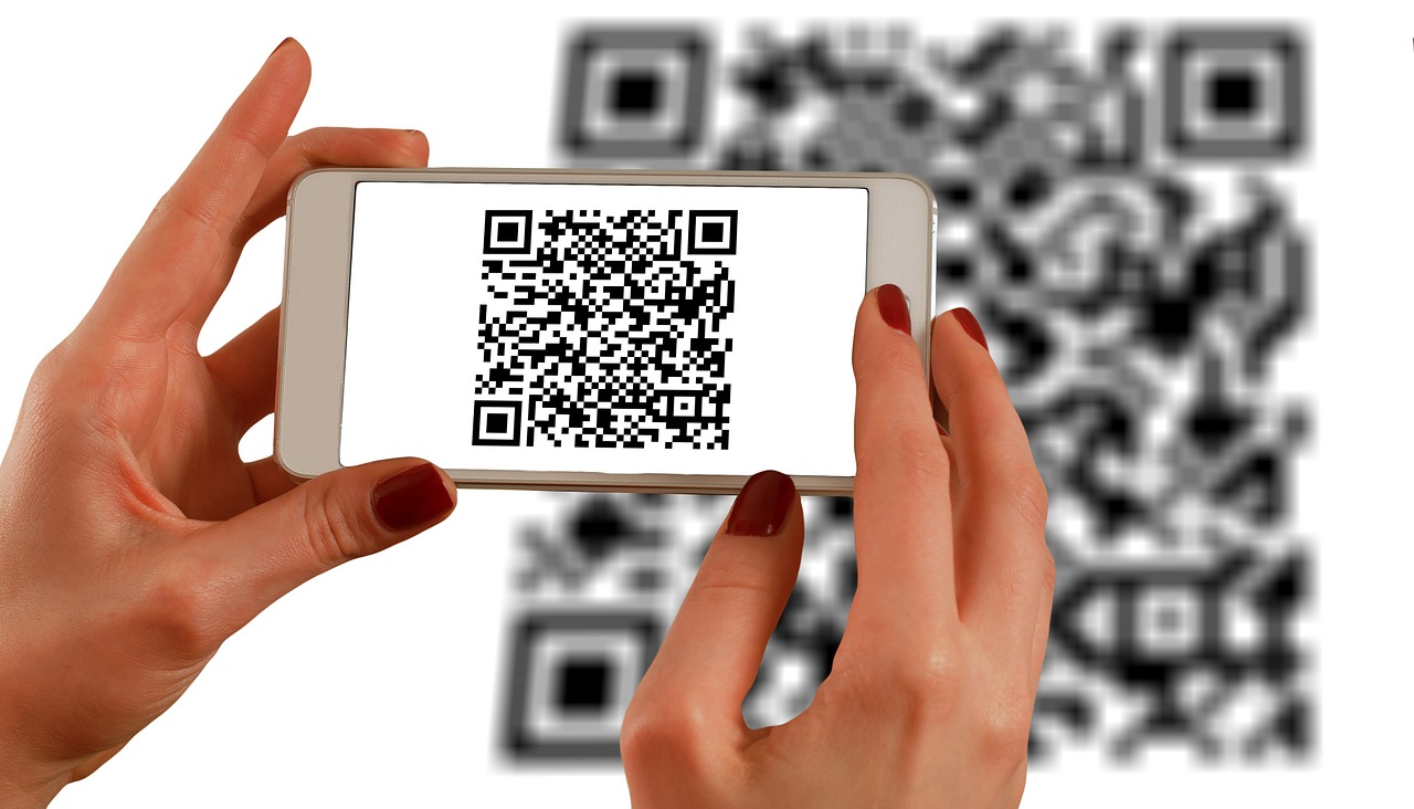 Image of a woman's hands holding an iPhone and scanning a qr code